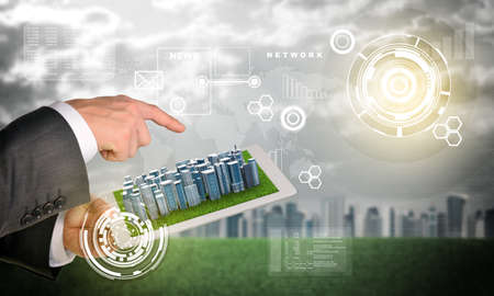 Man hands using tablet pc. Business city on touch screen. Virtual elements near tablet. City on background photo
