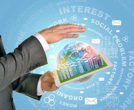 Man hands using tablet pc. Business city on touch screen. Earth as backdrop.   photo