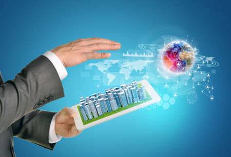 Man hands using tablet pc. Business city on touch screen. Earth near tablet.   photo