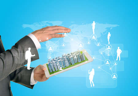 Man hands using tablet pc. Business city on touch screen. Network with business silhouettes near tablet photo