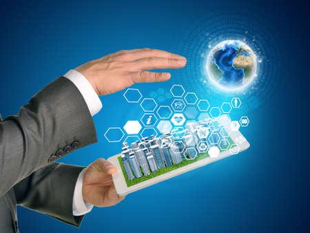 rectángulo: Las manos del hombre que usa la PC de la tableta. Ciudad de negocios en la pantalla táctil. Tierra y hexágonos con iconos cerca de la tableta.