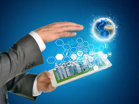 Man hands using tablet pc. Business city on touch screen. Earth and hexagons with icons near tablet.  photo