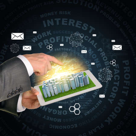 Man hands using tablet pc. Business city on touch screen. Business words near tablet photo