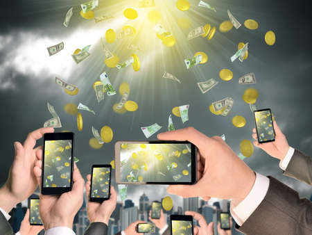 Hands holding smart phones and shoot video as falling money. City on background photo