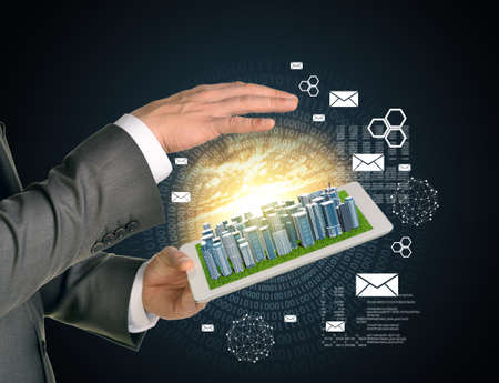 using tablet: Man hands using tablet pc. Business city on touch screen. Figures as backdrop.  Business concept Stock Photo