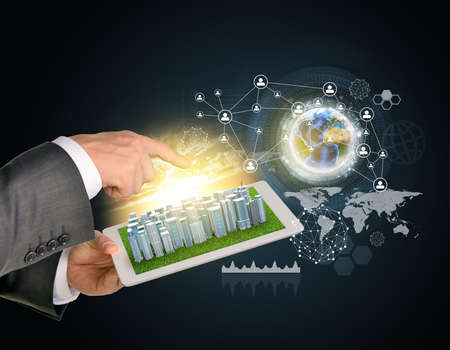 using tablet: Man hands using tablet pc. Business city on touch screen. Earth with network near computer.  Stock Photo