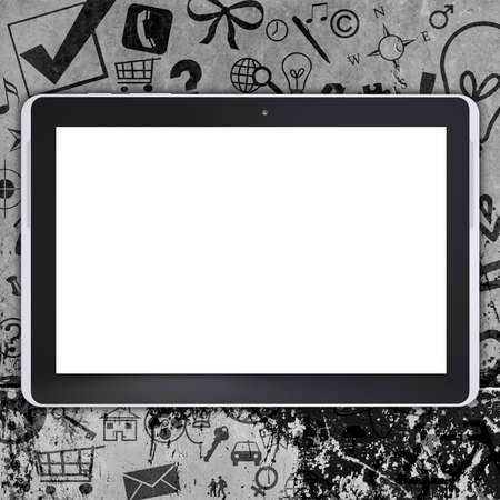 Tablet pc on concrete floor with various social icons. Computer concept photo