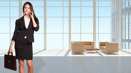 Businesswoman holding brifecase and using phone. Large window in office building as background photo