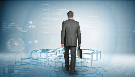 Businessman in suit holding briefcase and goes forward. Rear view. Wire-frame gears gear underfoot. Graphs as backdrop photo