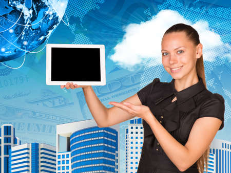 Beautiful businesswoman smiling and holding hand tablet with blank screen. Other hand points to tablet. Buildings, money and Earth as backdrop. Elements of this image furnished by NASA photo