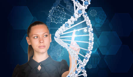 Beautiful businesswoman in dress presses finger on model of DNA. Scientific and medical concept photo