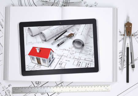 architect tools: Small house with drawings displayed on tablet screen. Under the tablet lying open book and drawings with tools of architect. Construction concept