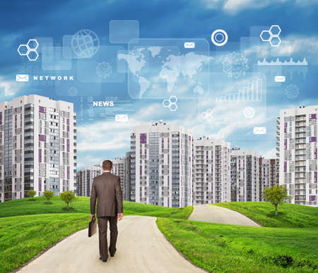Businessman in suit walking along road through green hills. City of tall buildings in background. Charts and other virtual items in sky. Business concept photo