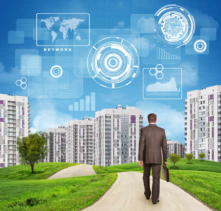 Businessman in suit walking along road through green hills. Rear view. City of tall buildings in background. Charts and other virtual items in sky. Business concept photo