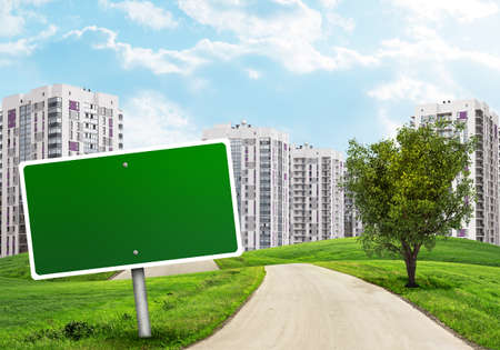 multi storey: Blank green billboard out of upright and tree by road running through green hills. High-rise buildings as backdrop Stock Photo