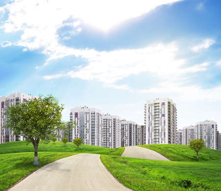 multi storey: Road through green hills with a few trees, leading to city. Green tree on the fore. High-rise buildings as backdrop