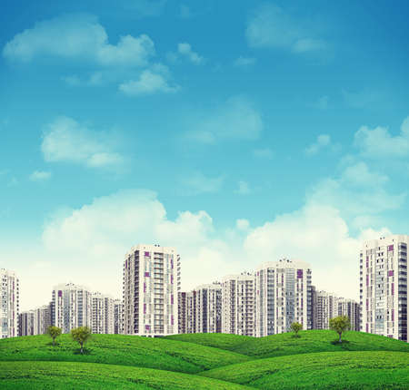 blue sky and fields: High-rise buildings of same design over grassy hills with a few trees.