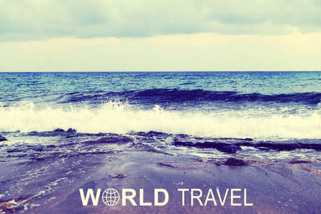 ashore: Sea wave rolling ashore. Inscription World Travel and related symbol Stock Photo