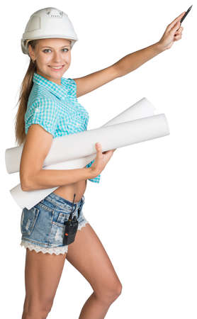 half turn: Beautiful girl in white helmet, shorts and shirt holding scrolls drawings and ballpoint pen indicates forward. Isolated over white background Stock Photo