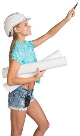 indicates: Beautiful girl in white helmet, shorts and shirt holding scrolls drawings and ballpoint pen indicates forward. Isolated over white background Stock Photo