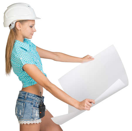 half turn: Beautiful woman builder in white helmet holding in front of him large sheet of paper. Isolated over white background