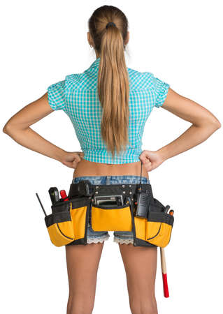 Pretty girl in shorts, shirt and tool belt with tools standing with hands on hip. Rear view. Isolated over white background photo