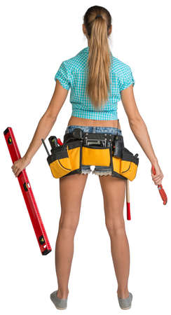 Pretty girl in shorts, shirt and tool belt with tools holding red building level and wrench. Full length rear view. Isolated over white background photo