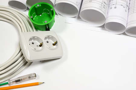 Drawing rolls, wall socket, socket box, power cable, test pen, pencil on white surface photo