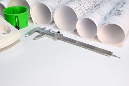 wall socket: Drawing rolls, wall socket, socket box, sliding calipers on white surface
