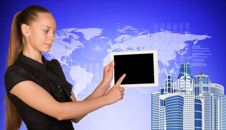 Business woman holds tablet PC, pointing at blank screen. High-rise buildings beside.On blue background with hi-tech graphs and world map. Business concept photo