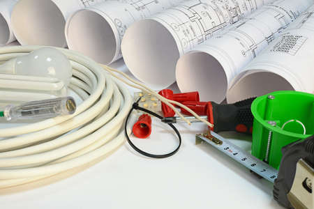 Drawing rolls, socket box, power cable, screwdriver and other tools on white surface photo
