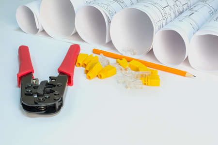 rj 45: Drawing rolls, crimping pliers, connectors, boot caps, pencil on white surface Stock Photo