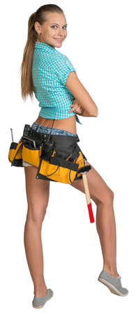 Pretty girl in shorts, shirt and tool belt with tools standing with crossed arms. Full length rear view. Isolated over white background photo