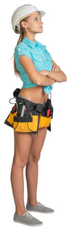Looking up pretty girl in helmet, shorts, shirt and tool belt with tools standing with crossed arms. Full length. Isolated over white background photo