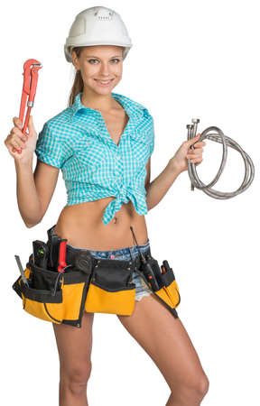 Pretty girl in helmet, shorts, shirt and tool belt with tools holding flexible hose and wrench. Isolated over white background photo