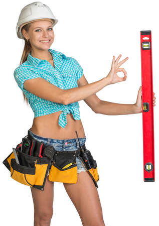 Beautiful girl in white helmet, shorts and shirt holding builders level and showing OK hand sign. Isolated over white background photo