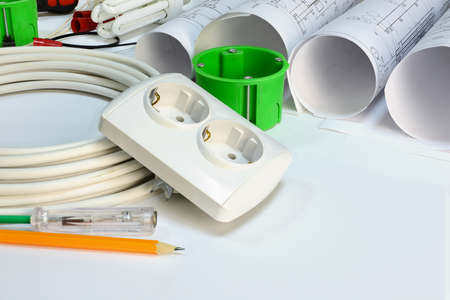 wall socket: Drawing rolls, wall socket, socket box, power cable, screwdriver, lamp, test pen, pencil, fastener and wire connectors on white surface