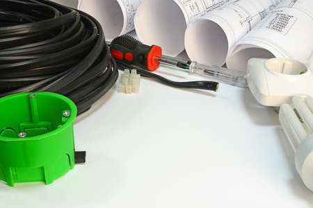 mounting: Drawing rolls, triple cable, screwdrivers, test pen, terminal block, wall socket, socket box, lamp on white surface Stock Photo