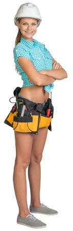 Pretty girl in helmet, shorts, shirt and tool belt with tools standing with crossed arms. Full length. Isolated over white background photo