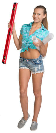 belly button girl: Pretty woman in shorts and shirt smiling and holding paper scrolls and red building level. Full length. Isolated over white background