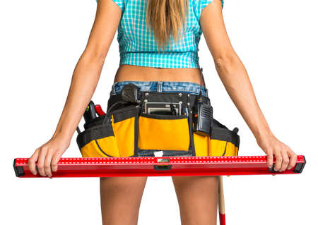 Woman wearing shirt. shorts and tool belt with tools holding builders level behind her, close up, back view, isolated on white background photo