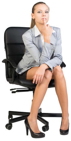 half turn: Businesswoman on office chair, looking at camera, holding her forefinger at her lower lip. Isolated over white background Stock Photo