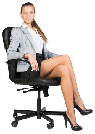 ooking: Businesswoman in office chair, ooking at camera, with straight back and crossed legs. Isolated over white background