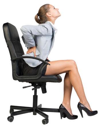 Zakenvrouw met pijn in de onderrug van het zitten op bureaustoel. Geïsoleerd over witte achtergrond