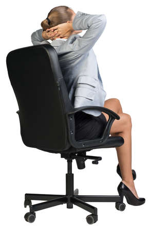 clasped: Businesswoman sitting back in chair, half-turn from behind, with her legs crossed and her hands clasped behind her head. Isolated over white background Stock Photo