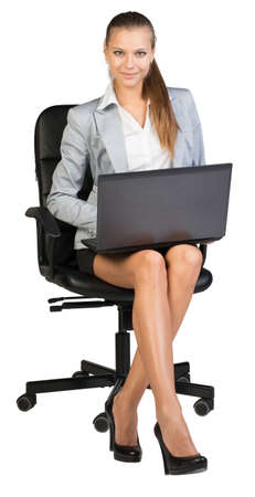half turn: Businesswoman on office chair, with laptop on her knees, looking at camera, smiling. Isolated over white background Stock Photo