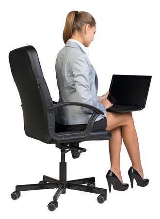 Businesswoman on office chair, half-turn from behind, with laptop on her knees, looking at empty black screen. Isolated over white background photo