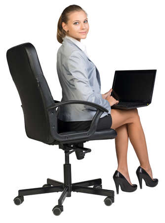 Businesswoman on office chair, with laptop on her knees, looking at camera, smiling. Isolated over white background photo