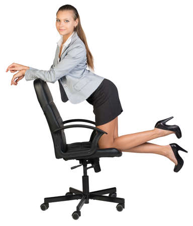 half turn: Businesswoman kneeling on office chair, her arms on chair back, looking at camera cheerfully. Isolated over white background Stock Photo