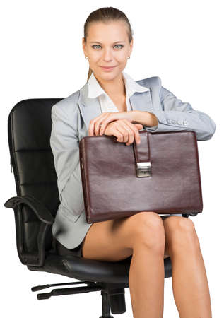 Businesswoman on office chair, looking at camera cheerfully, holding suitcase on her knees. Isolated over white background photo